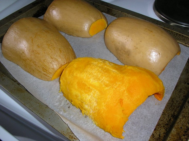 Baked pumpkins. One has been peeled.